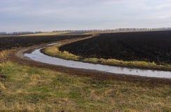 Ajardine com uma estrada de terra entre campos na estação outonal atrasada em Ucrânia central Foto de Stock Royalty Free