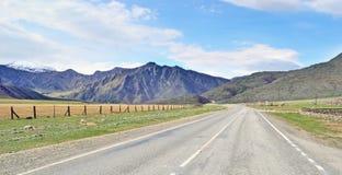 Ajardine com uma estrada do automóvel em uma área montanhosa Imagens de Stock