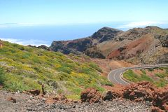 Ajardine com uma estrada nas montanhas e o oceano no fundo Imagens de Stock Royalty Free