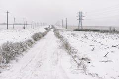 Ajardine com uma estrada vazia da terra entre campos agrícolas na estação do inverno em Ucrânia central Imagem de Stock