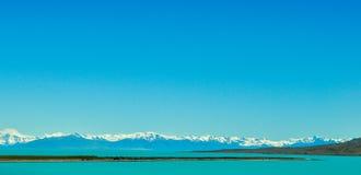 Ajardine com uma lagoa azul esverdeado com montanhas neve-tampadas dentro Imagem de Stock