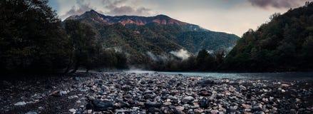 Ajardine com uma praia de pedra no rio e o cume arborizado no por do sol Imagens de Stock