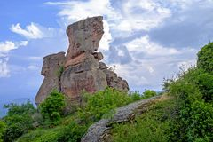 Ajardine com uma rocha velha contra um céu nebuloso 2 Fotografia de Stock Royalty Free