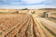 Ajardine com uma terra arada e uma estrada secundária em Cuencabuena, Teruel Foto de Stock Royalty Free
