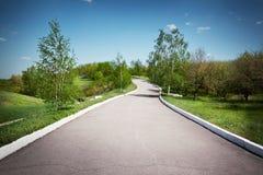 Ajardine com uma trilha do asfalto em um parque Fotos de Stock Royalty Free