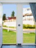 Ajardine com uma vista através de uma janela com cortinas Imagens de Stock Royalty Free