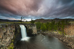 Ajardine com uma vista da cachoeira e do céu bonito Imagem de Stock