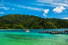 Ajardine com uma vista da praia, do mar e do cais na ilha Fotos de Stock Royalty Free