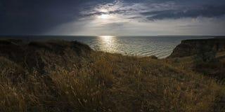Ajardine com uma vista da praia no por do sol Imagem de Stock