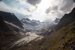 Ajardine com uma vista das montanhas e de uma geleira de derretimento Fotos de Stock Royalty Free