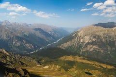 Ajardine com uma vista das montanhas e do céu azul Foto de Stock