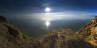Ajardine com uma vista do estuário do mar no por do sol Fotos de Stock Royalty Free
