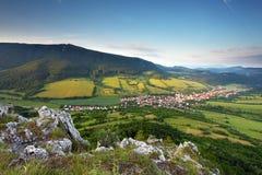 Ajardine com vila, montanhas e o céu azul Imagens de Stock