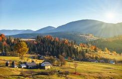 Ajardine com vila, montanhas e o céu azul Imagem de Stock