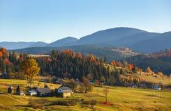 Ajardine com vila, montanhas e o céu azul Fotos de Stock