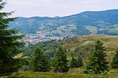 Ajardine com vila, montanhas e o céu nebuloso Foto de Stock