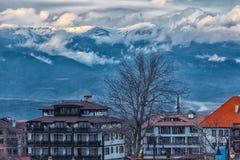 Ajardine com vista na cidade pequena com montanhas e nuvens Fotografia de Stock Royalty Free