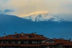 Ajardine com vista na cidade pequena com montanhas e nuvens Foto de Stock