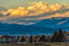 Ajardine com vista na cidade smal com montanhas e nuvens Fotos de Stock Royalty Free