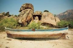 Ajardine con el barco viejo del pescador abandonado en la tierra seca Foto de archivo