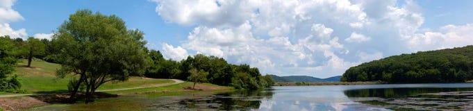 Ajardine con el bosque del lago, la montaña y el cielo azul Imagen de archivo