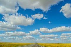 Ajardine con el cielo grande con las nubes y la barra en el medio de los campos amarillos fotos de archivo