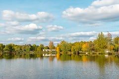Ajardine con el lago, el cielo nublado, y los árboles reflejados simétricamente en el agua Lago salt Sosto Nyiregyhaza, Hungría fotos de archivo