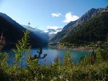 Ajardine con el lago, las montañas y el cielo azul imagen de archivo