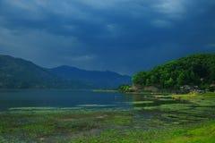 Ajardine con el lago y las montañas antes de la tormenta Foto de archivo