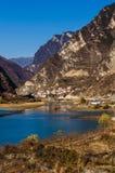 Ajardine con el pueblo ocultado entre el agua y la montaña Foto de archivo