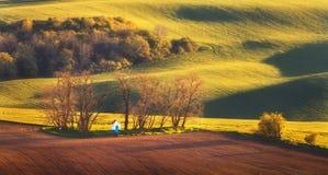 Ajardine con la capilla, árboles en campo verde en la puesta del sol Fotos de archivo libres de regalías