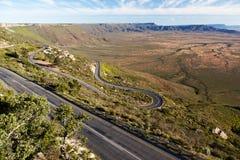 Ajardine con la carretera que serpentea abajo en el valle Imagenes de archivo