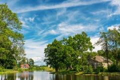 Ajardine con la casa, el lago, los árboles y el cielo imagenes de archivo