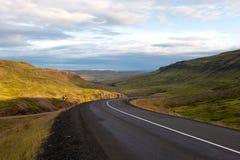 Ajardine con las montañas y el camino de serpenteo en la puesta del sol, Islandia Imagen de archivo libre de regalías
