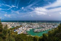 Ajardine con los árboles verdes y los barcos de la navegación y de placer se abrigan en fondo Fotografía de archivo libre de regalías
