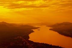 Ajardine con puesta del sol en la montaña y el río de la silueta Imagenes de archivo