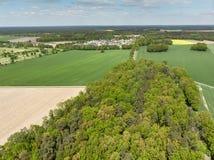Ajardine con un bosque, los prados y los campos y un pequeño pueblo en el fondo, visión aérea desde una altura de 100 metros Fotografía de archivo libre de regalías