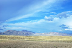 Ajardine con un valle y las montañas de la montaña en la distancia Foto de archivo