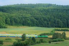 Ajardine con una línea ferroviaria, un tren, colinas y FO Fotos de archivo
