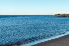 Ajardine a costa e a parte do cabo de pedra no horizonte Foto de Stock Royalty Free