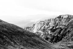 Ajardine das montanhas de Bucegi, em Romênia em um dia muito nevoento Fotos de Stock