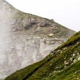 Ajardine das montanhas de Bucegi, parte de Carpathians do sul em Romênia em um dia nevoento Fotografia de Stock Royalty Free