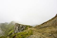 Ajardine das montanhas de Bucegi, parte de Carpathians do sul em Romênia em um dia nevoento Fotografia de Stock