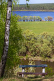 Ajardine de la altura con los bancos debajo de un abedul en un fondo del río de Desna con los prados y los bosques Foto de archivo