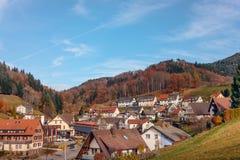 Ajardine el campo del otoño con los cortijos de madera en la colina verde y las montañas rugosas en el fondo ~ vista idílica del  Imágenes de archivo libres de regalías