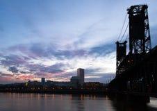 Ajardine el puente y el saturat del río de la silueta del horizonte de la ciudad de la noche Foto de archivo