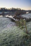 Ajardine el surnise del invierno del río y de campos escarchados Fotos de archivo libres de regalías