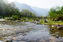 Ajardine el tiro con las pequeñas colinas y la luz del sol del río durante mornin Fotos de archivo