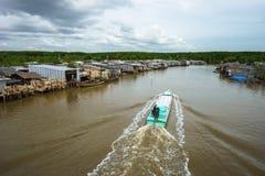 Ajardine em Ca Mau com o barco de madeira que corre ao longo da vila de flutuação no delta de Mekong, Vietname sul Fotos de Stock