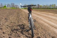 Ajardine em Ucrânia com uma estrada de terra entre campos arávéis agrícolas e bicycle esperando o passeio Imagem de Stock